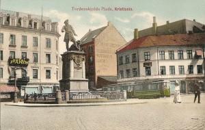 Tordenskiolds plass i Kristiania med Tordenskioldstatuen og Hotel Paris i bakgrunnen. Håndkolorert postkort fra ca. 1905, tilhører Oslo Byarkiv. Fra Oslobilder.